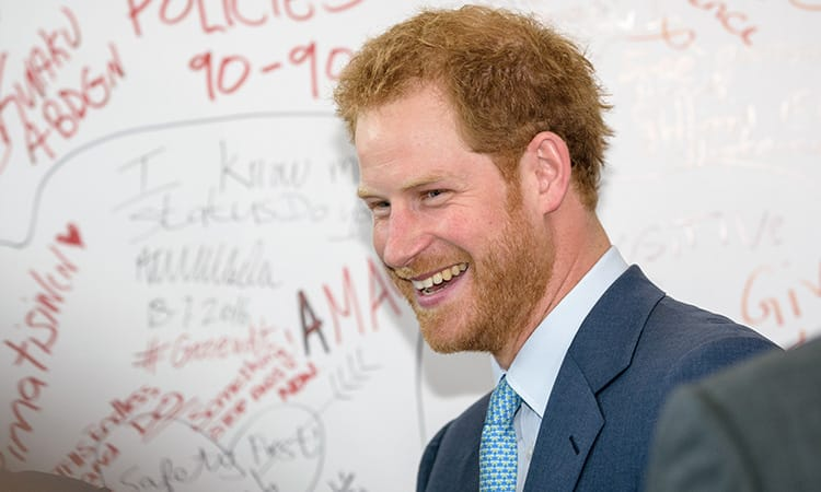 Prince Harry turning to the side and laughing