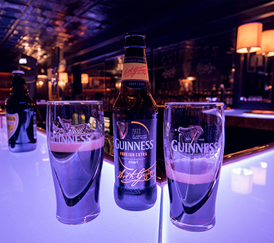 A bottle of Guinness and two glasses on the bar in The Guinness Factory, Dublin