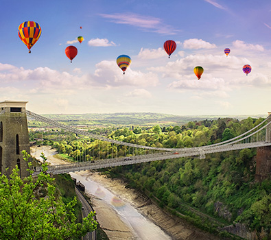 Some hot air balloons in Bristol, flying above a high level bridge