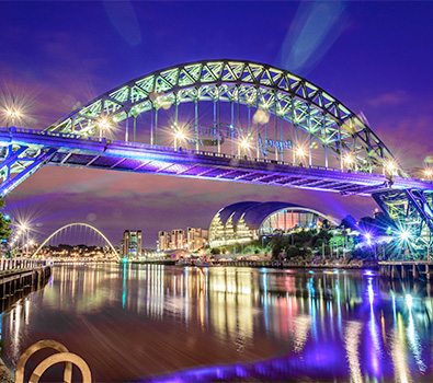 The Tyne Bridge, The Sage and The Millenium Eye all illuminated at night along the Quayside