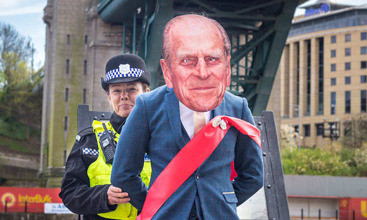 A Last Night of Freedom staff member wearing a Prince Philip mask, with a police officer behind him