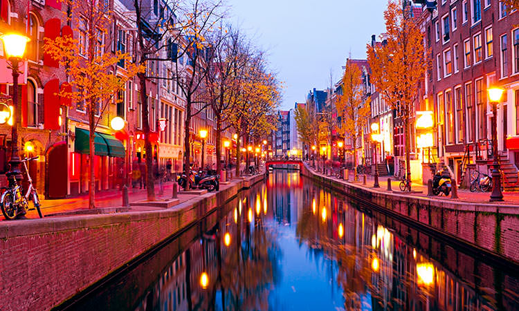 A shot of one of the canals in Amsterdam at night with beautiful townhouses reflecting off the water