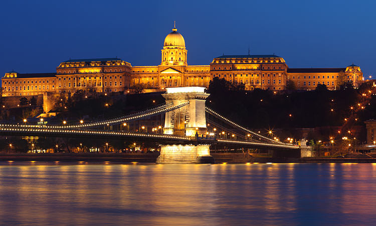 The Szechenyi Bridge crossing the Danube River at night with the Buda Castle in the background on the hill
