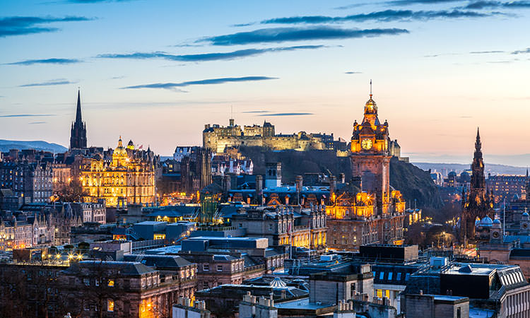 A view over the building tops of Edinburgh with the castle on the top of the hit as the sun goes down.