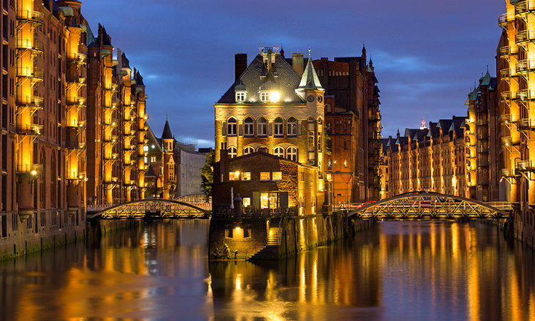 A picture of the Hamburg canal with traditional German architecture lit up around it.
