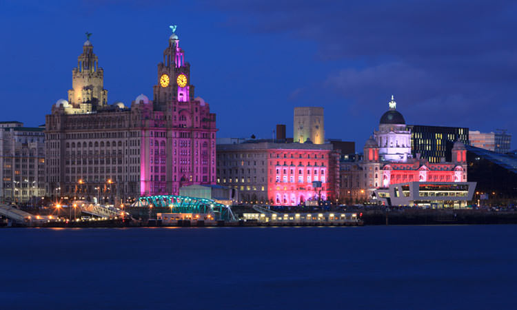 The famous Royal Liver Building illumintaed with a pink light with the River Mersey in the foreground