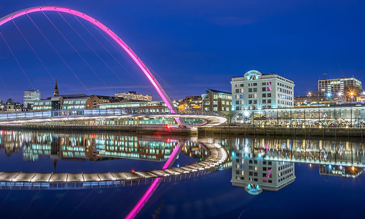 Newcastle's Quayside at night with the Millenium Bridge in the foreground over the River Tyne