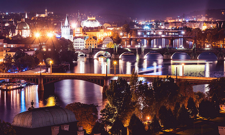 The famous Charles bridge is illuminated at night by the lit up cityscape behind