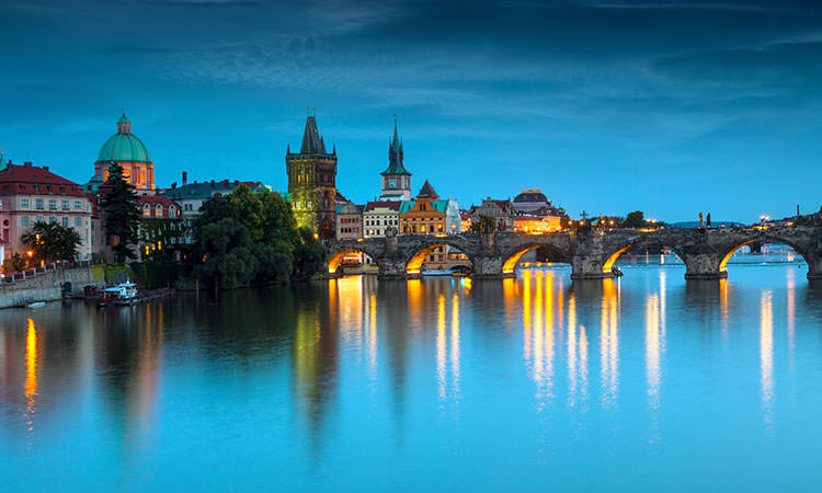 The Charles Bridge with lights reflecting off the bridge onto the water of the Vltava river