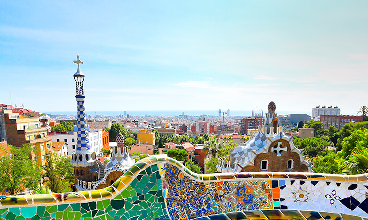 A view of the Barcelona skyline during the day with a colourful mosaque wall in the fore-ground.
