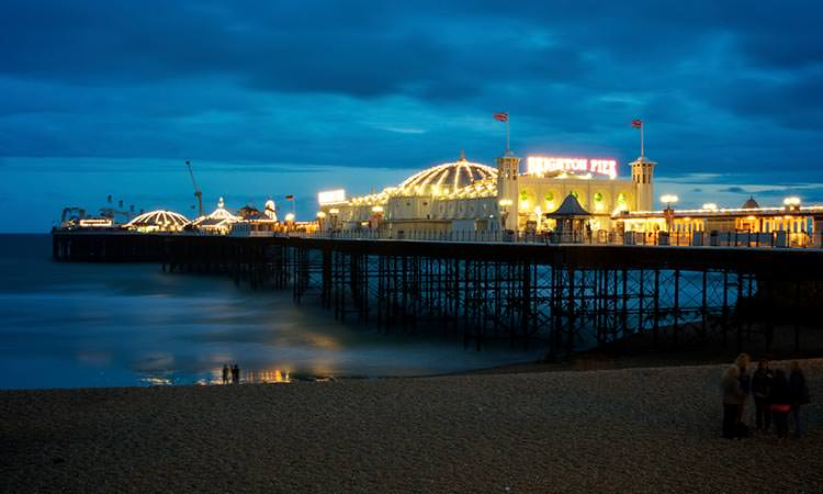 View of Brighton Pier from the beach at night with group of people in the foreground on the beach