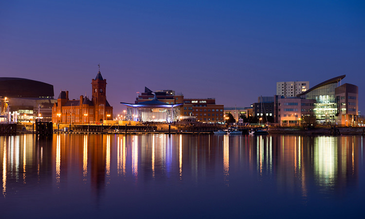 A view of Cardiff waterfront lit up at night.