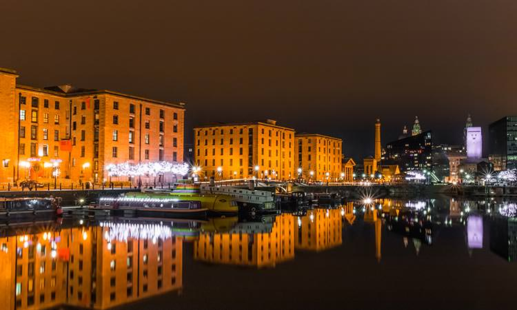 Liverpool's Docklands at night with the city skyline in the background.