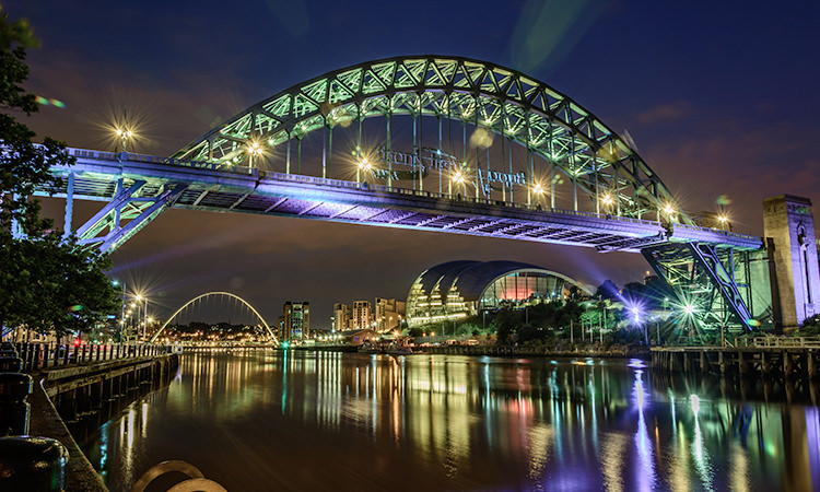 The Tyne bridge lit up at night with lights from the Sage and Millennium Bridge reflecting on the River Tyne