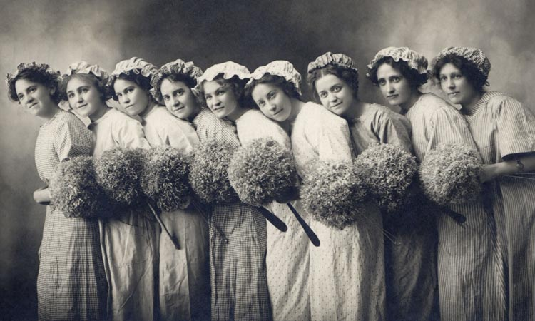 A black and white image of nine women in dresses, holding flowers