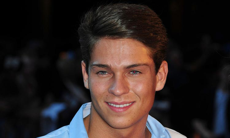 A head shot of Joey Essex wearing a blue shirt