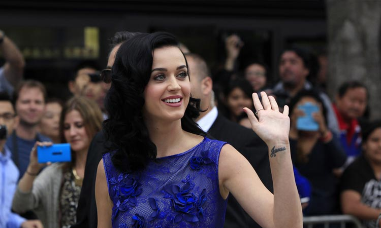 Katy Perry wearing a blue dress and waving