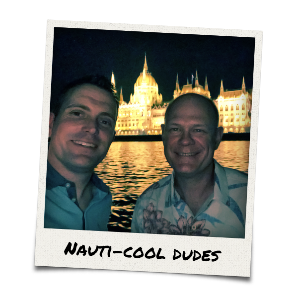 Two men on a boat in front of the Hungarian Parliament Building