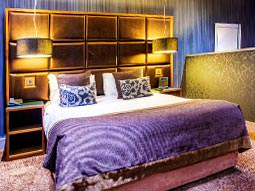 A double bed with purple bedding and atmospheric lighting