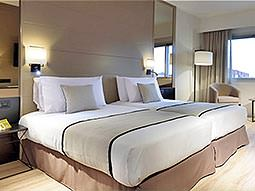 Two double beds with cream throws and cushions, in a hotel room