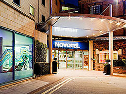 The lit-up entrance of the Novotel, Cardiff, at night
