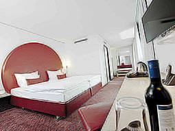 Two beds in a hotel room, with a desk in the foreground and topped with a bottle of red wine