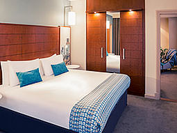A double bed in a blue hotel room, with dark wood cupboards along the wall