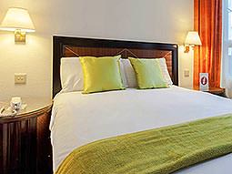 A bedroom within Britannia Hotel with white and lime green bedding