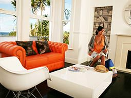 A woman sat at a chair and reading a magazine, next to a leather orange sofa, coffee table and other white chair