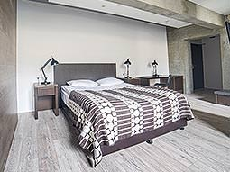 A double bed in a large, Scandinavian-styled guest room