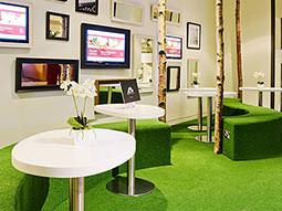 Tables and green seats on a green carpet, in front of a wall lined with pictures