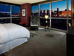 A guest room with panoramic floor-to-ceiling windows offering views over Las Vegas at night