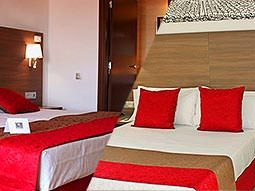 Split image of double beds topped with red cushions and a red and brown throw