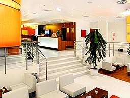 The Star Inn Hotel Centru lobby, with white seating in the foreground and a reception desk in the back