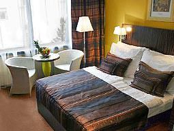 A double bed, topped with a throw and two cushions, with two chairs and a table in the background