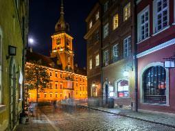 A street-lit Warsaw street at night