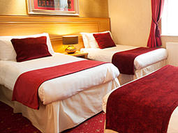 Two twin beds, with red throws and cushions placed on top, in a hotel room