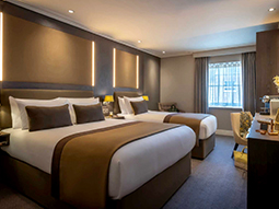 A large guest room at the Belvedere Hotel with double and twin beds