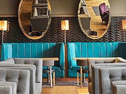 Some teal coloured chairs with mirrors above them