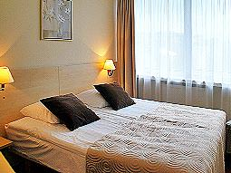 A double bed in a room with brown and cream bedding