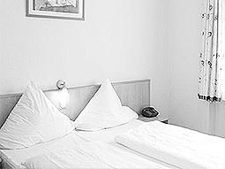 A white guest room with two twin beds