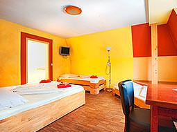 A large guest room with multiple beds, a desk and yellow walls