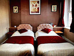 Two single beds in a hotel room, with red cushions and throws on top