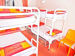 Two white bunk beds with red and orange blankets folded on top, placed next to a plastic orange chair