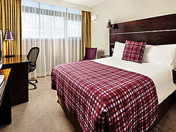 A double bed in a hotel room, with a purple tartan throw and cushion on top