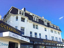 The exterior of Ocean Beach Hotel under a blue sky