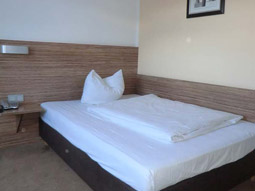 A twin bedroom with brown and lime green decor
