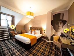 A double bed in a hotel room, topped with a yellow throw, with a desk in the corner and a large mural of a Victorian man on the wall