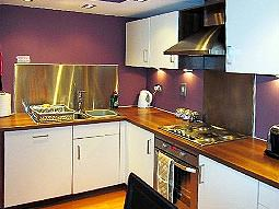 A purple kitchen with white cabinets