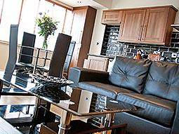 A leather sofa and glass coffee table, with a dining table and kitchenette in the background